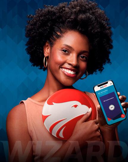 Mulher negra sorrindo e segurando um celular com a mão esquerda com a tela virada para frente. Com a mão direita segura um brasão vermelho com águia branca.
