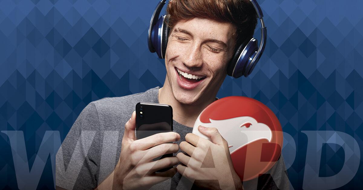 Homem branco sorrindo e com olhos fechados, cabelos castanhos e camiseta cinza com headfone na cabeça. Ele está segurando um brasão vermelho com águia branca na mão esquerda e um celular na mão direita.