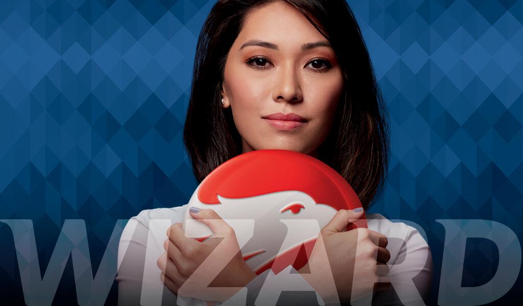 Mulher branca japonesa com cabelos lisos na altura do ombro e com camisa branca segurando um brasão vermelho com águia branca.