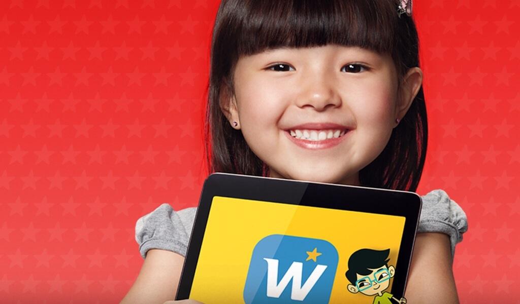 Menina japonesa segurando tablet com logo inglês para crianças Wizkids