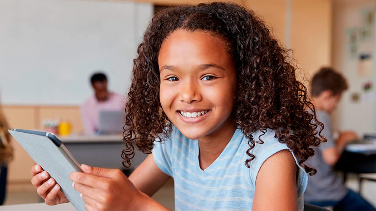 criança menina de vestido azul com um tablet na mão