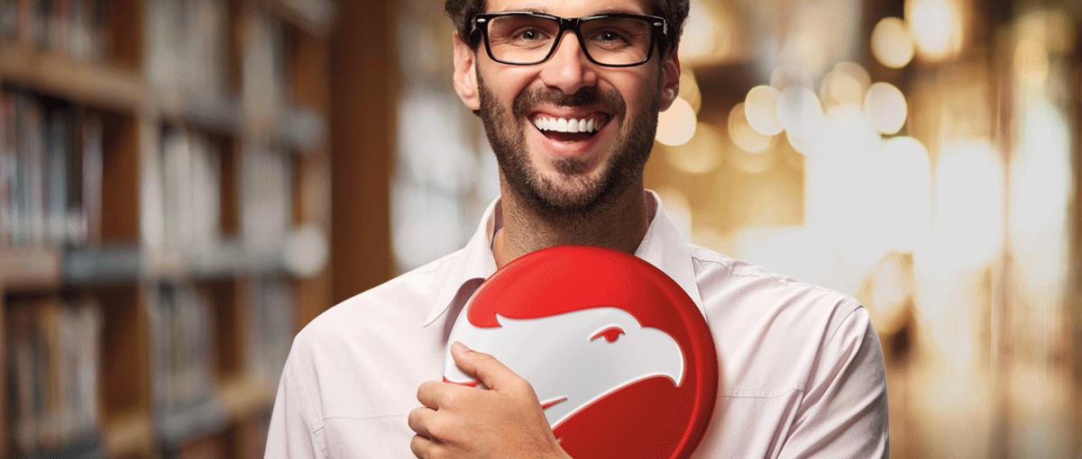 Homem branco de óculos e barba segurando brasão da escola Wizard by Pearson