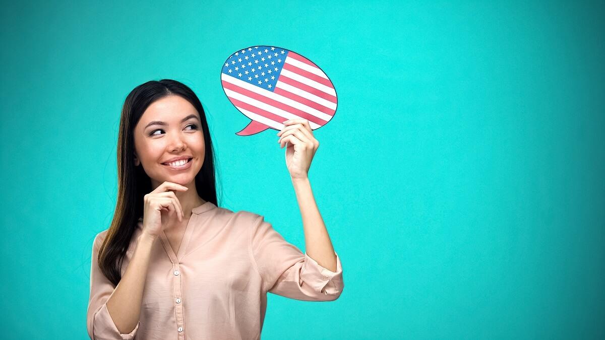 menina com camiseta rosa segurando um balão com bandeira dos estados unidos e fundo azu