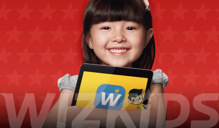 Menina japonesa segurando tablet com logo Wizkids em baixo
