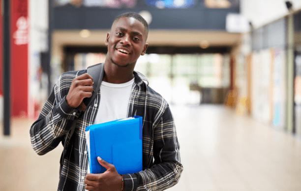 Homem negro segurando cadernos na escola