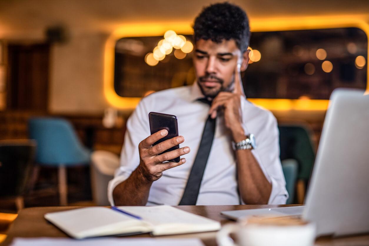 Homem empresário sentado numa mesa com computador e livros enquanto o olha o celular que está em sua mão, demonstrando que está trabalhando.