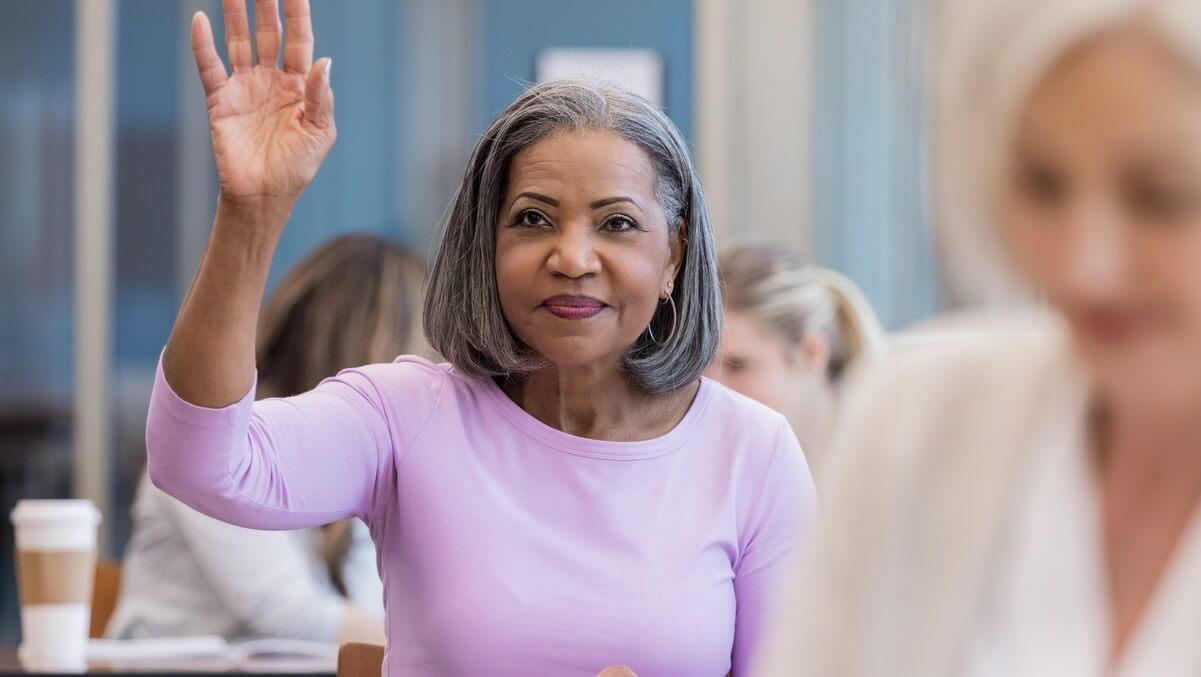 Mulher levantando a mão para tirar uma dúvida