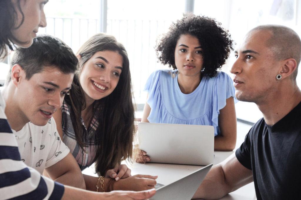 Cinco jovens sentados ao redor de uma mesa em uma reunião sobre franquias de idiomas.