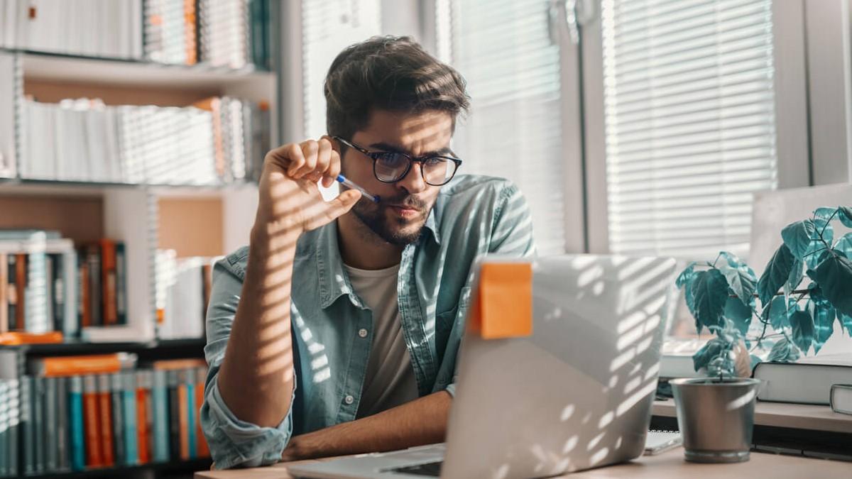 Homem jovem sentado nume mesa olhando a tela de um computador