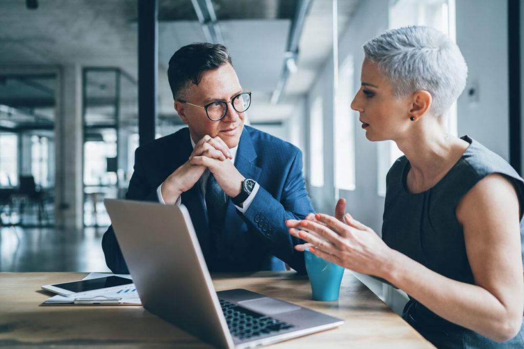 Homem e Mulher conversando e ao mesmo tempo olhando para a tela do computador