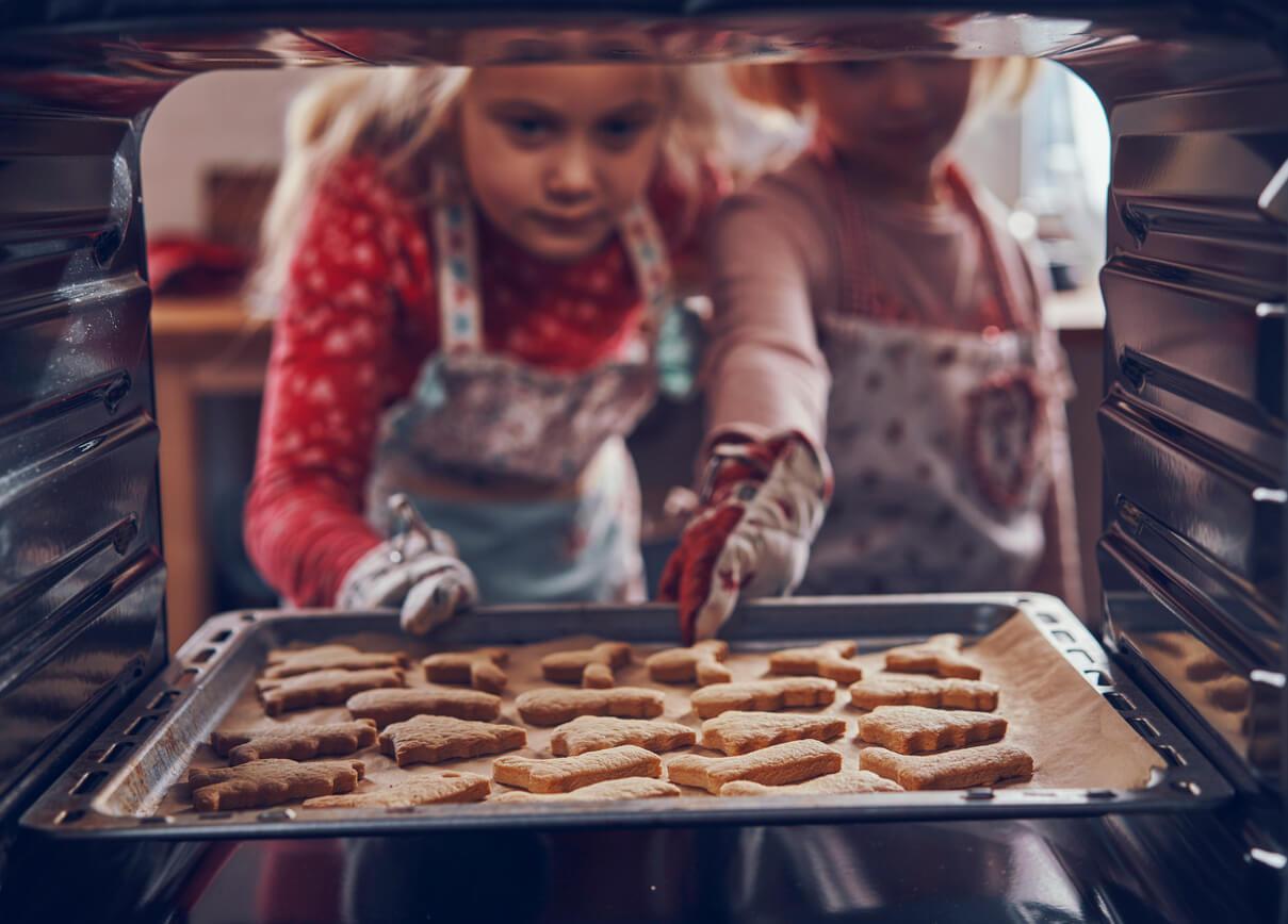 Duas meninas tirando uma bandeja de cookie do forno.