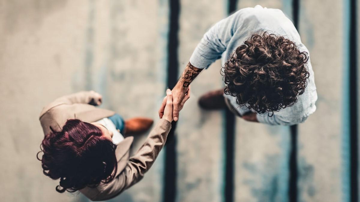 Homem e mulher apertando as mãos, simbolizando o fechamento de um negócio
