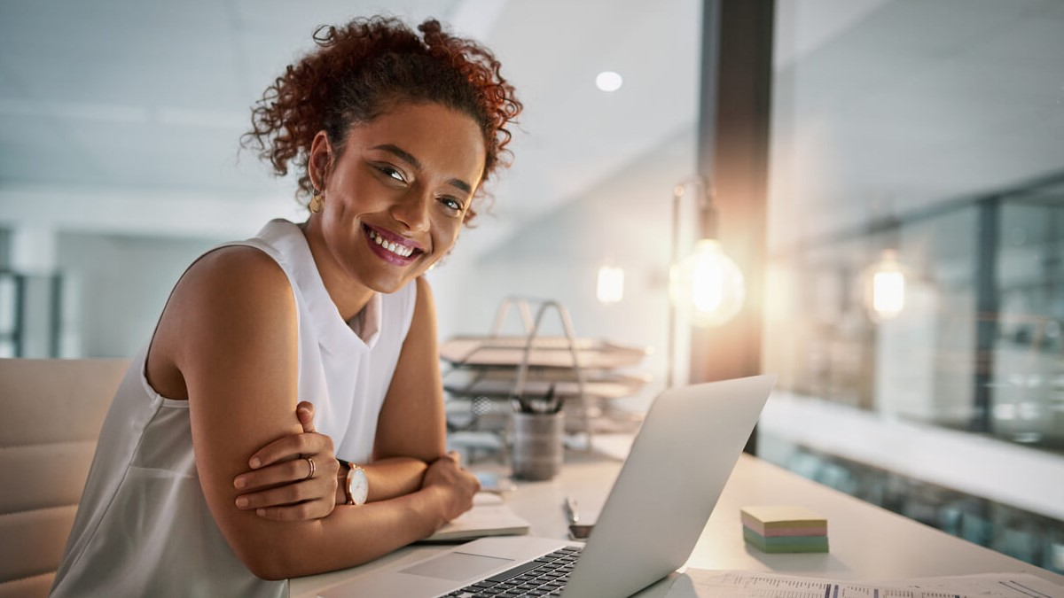 Mulher jovem com um computador na mesa e olhando para a câmera sorrindo