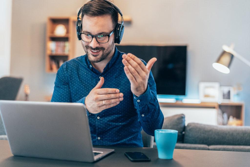 Homem fazendo home office com fone de ouvido, olhando para a tela do computador e gesticulando com a mão.