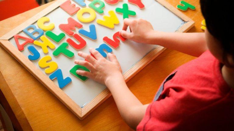 Criança brincando com uma lousa cheia de letras do alfabeto em plástico