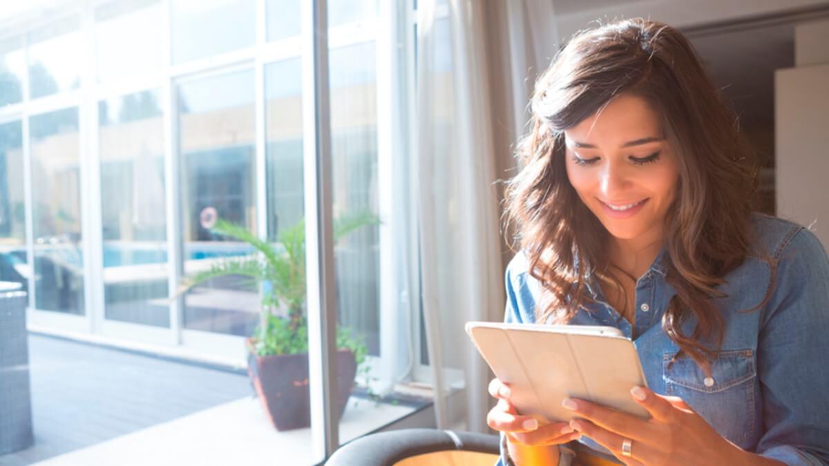Jovem olhando pro seu iPad e lendo livros em inglês