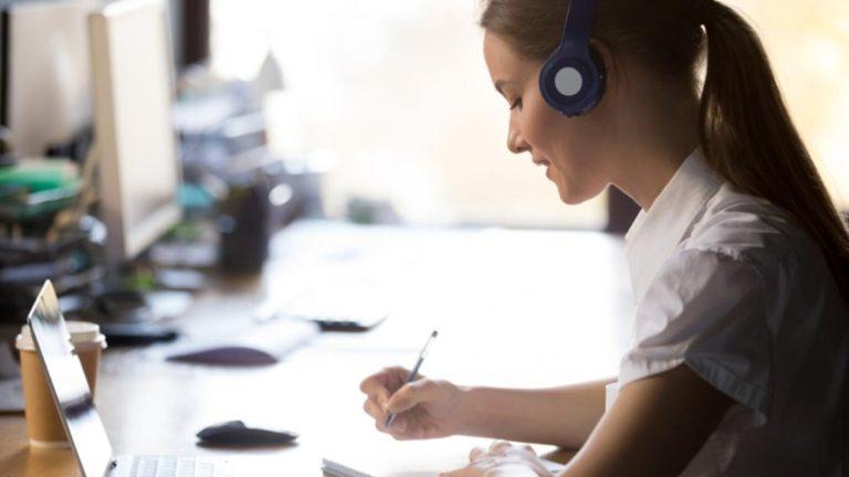 Menina estudando com alguns livros sob a mesa e com fones de ouvido
