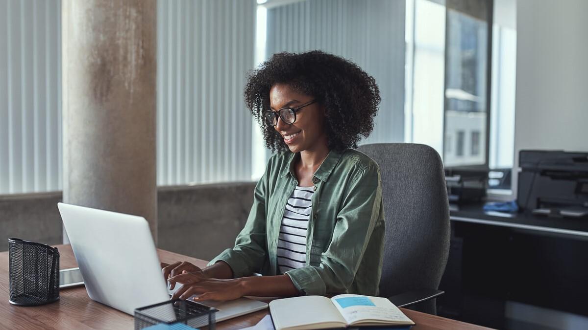 Mulher jovem olhando seu computador que está em cima de uma mesa com alguns papeis de anotações