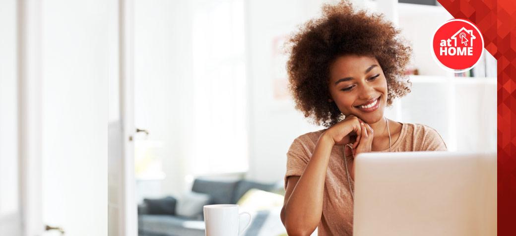 Mulher negra sentada na mesa olhando para notebook com mão no queixo
