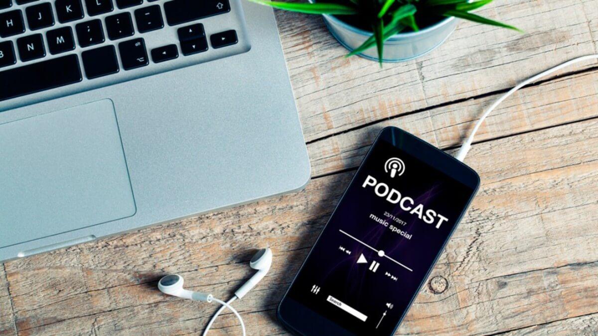 Imagem da tela de um celular com fones de ouvido. Na tela tem um podcast em inglês tocando.