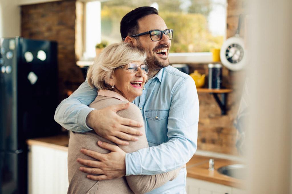 Homem jovem abraçando sua mãe em comemoração ao Dia das Mães