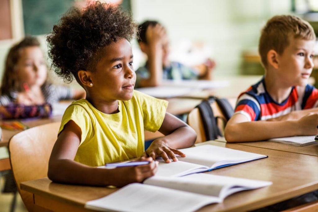 Uma menina em sala de aula infantil fazendo suas anotações em inglês