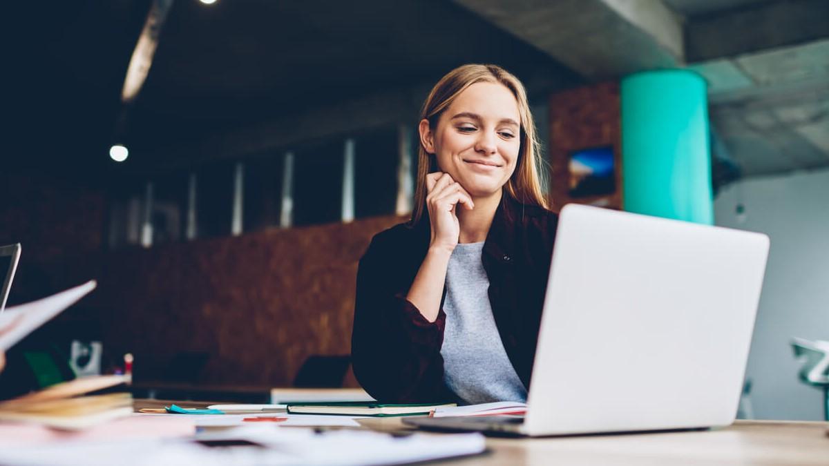 Mulher com um computador e caderno na mesa anotando termos de franquias
