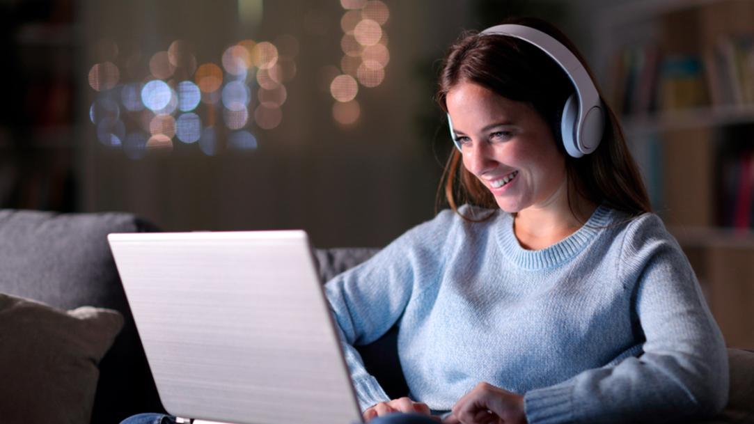 Mulher jovem assistindo séries em inglês no seu computador