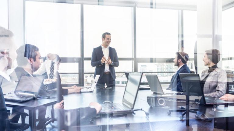 Homem em uma sala profissional com outros colegas da área