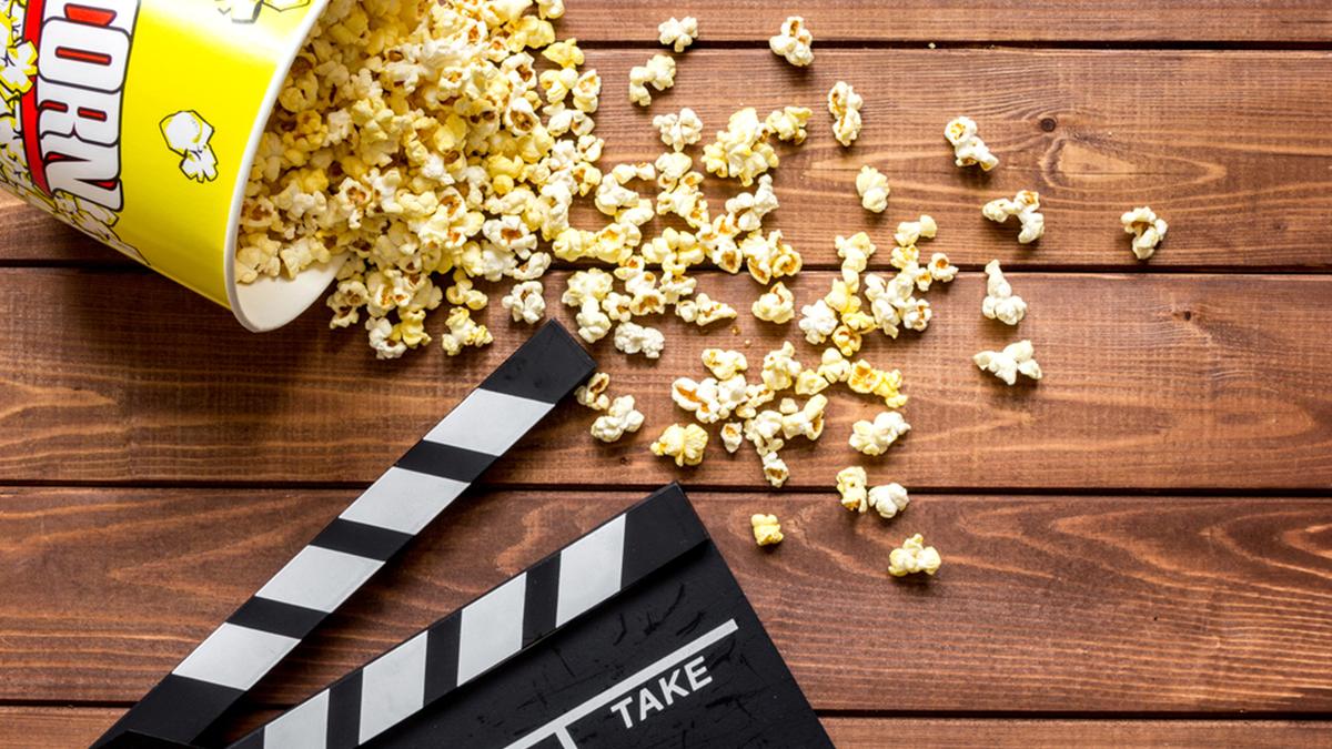 Imagem de um balde de pipoca e da placa de diretores de cinema