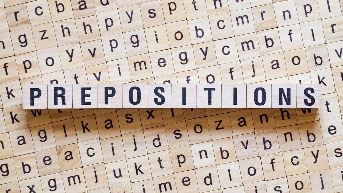 Cubos de madeira com letras formando a palavra prepositions