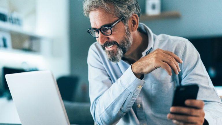 Homem com cabelo e barba grisalhos olhando a tela de um notebook e com seu celular na mão esquerda