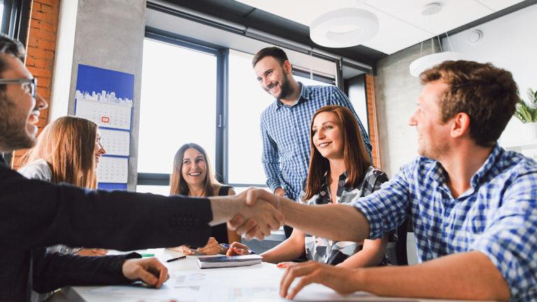 Sala de reunião com profissionais se cumprimentando