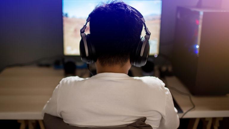 Menino de costas, sentado em uma mesa com um computador, jogando game de battle royale