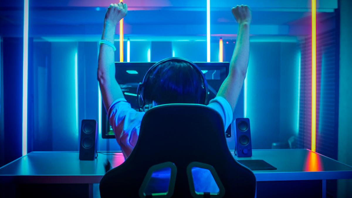 Menino com braços pra cima comemorando vitória em jogo online, sentado em uma cadeira em uma mesa com um computador