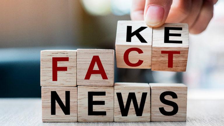 Cubos de madeira com letras que formam a palavra fake news