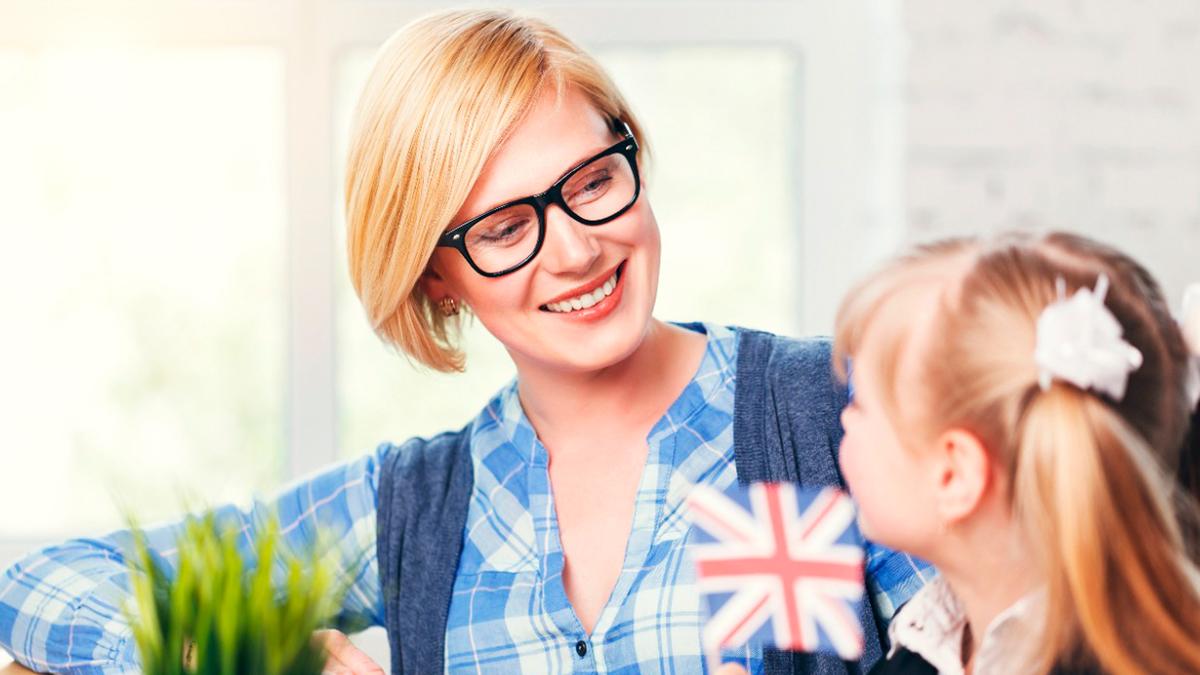 Mulher loira olhando para uma menina também loira com uma pequena bandeira inglesa entre elas