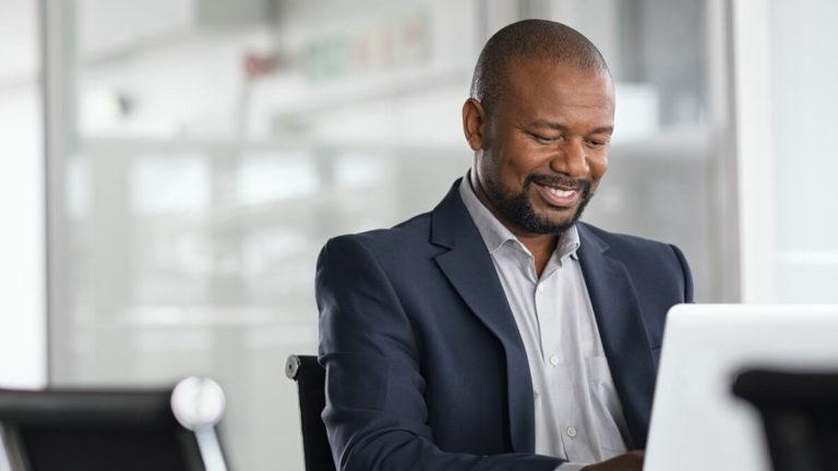 Homem negro sorrindo, aproximadamente 50 anos, sentado em uma mesa de escritório e olhando para um notebook