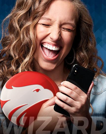 Garota loira sorrindo segurando um smartphone na mão e abracada no simbolo da Wizard
