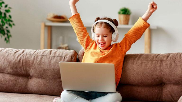 Menina loira sentada no sofá com um notebook no colo, os braços pra cima e um fone de ouvido