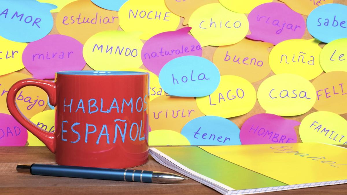 Uma caneca vermelha e muitos post-its ao fundo com palavras em espanhol