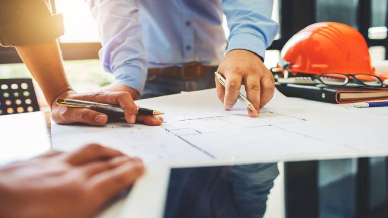 Dois pares de mãos sob uma mesa com projetos e um capacete de construção