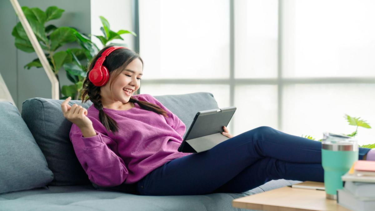 Garota pré-adolescente sentada em uma sofá, com um tablet na mão e fones de ouvido