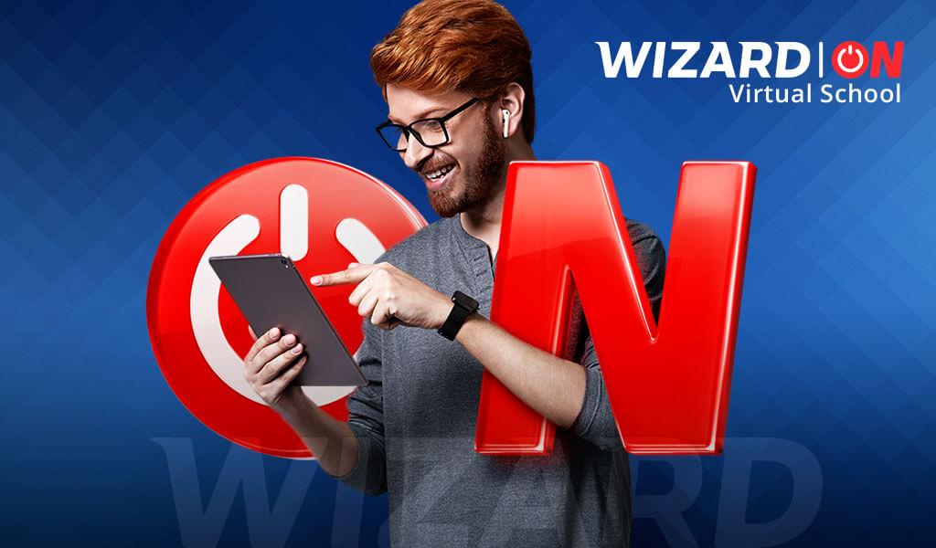 Rapaz de cabelos ruivos de óculos sorrindo com um tablet na mão posicionado entre as letras ON