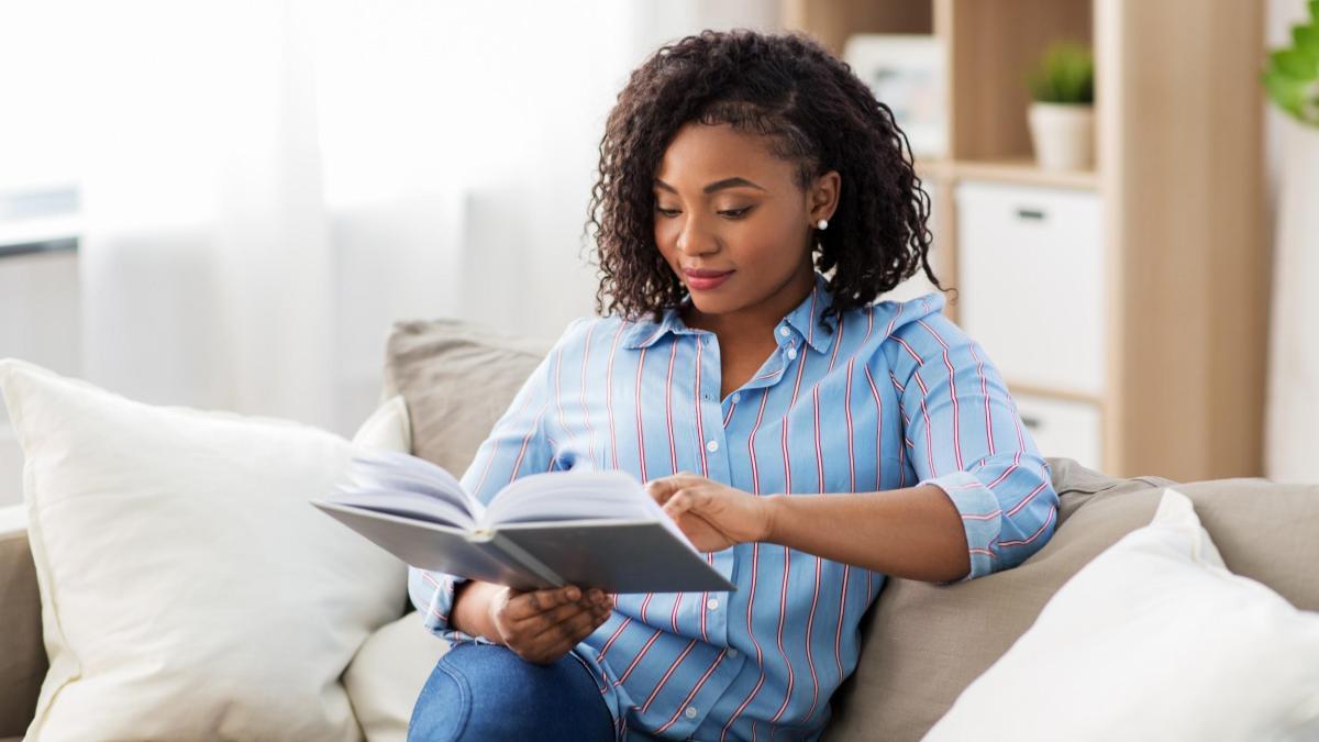 Mulher negra vestindo calça jeans e camisa azul, sentada em um sofá branco, lendo um livro