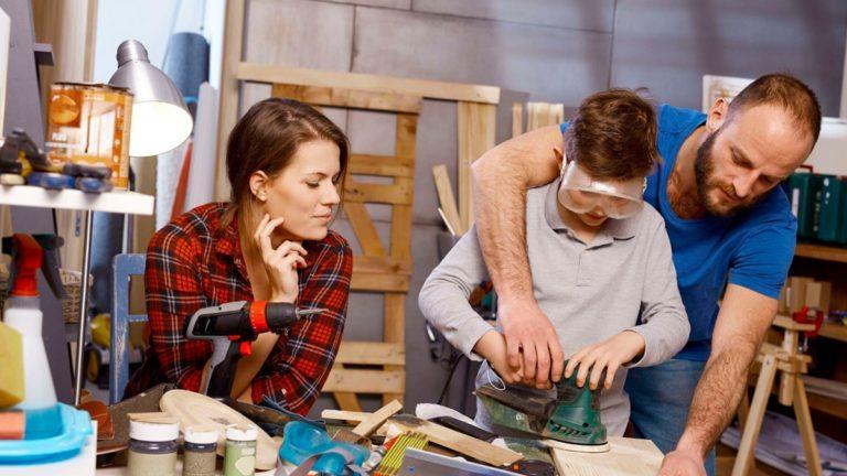 Uma mulher de camisa xadrez e um homem de camiseta azul ajudam seu filho a montar um objeto de madeira