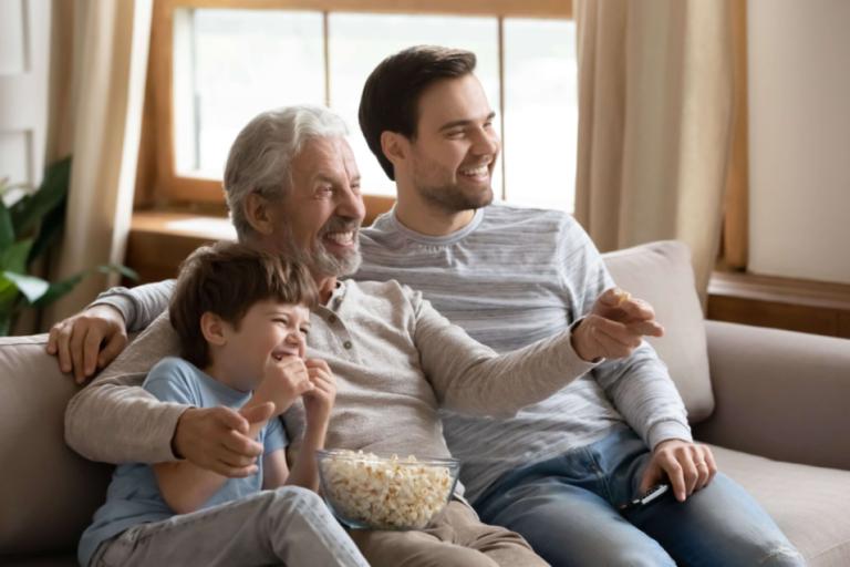 Um senhor, um homem adulto e um menino sentados em um sofá, o idoso segura um controle remoto de TV