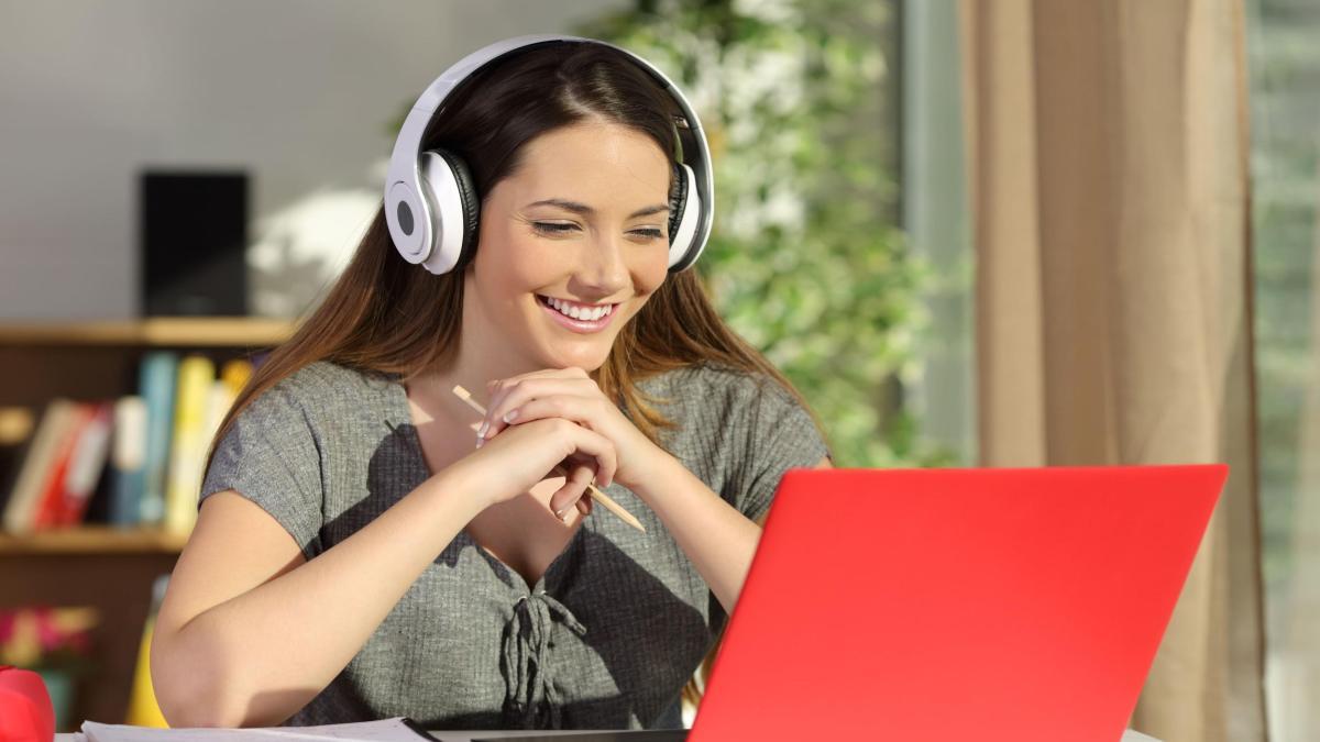Mulher branca de cabelo castanho e blusa verde, usando um fone de ouvido e olhando para um notebook
