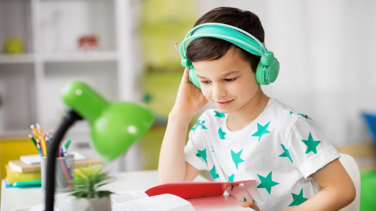 Garoto com fones de ouvido verdes segurando um tablet