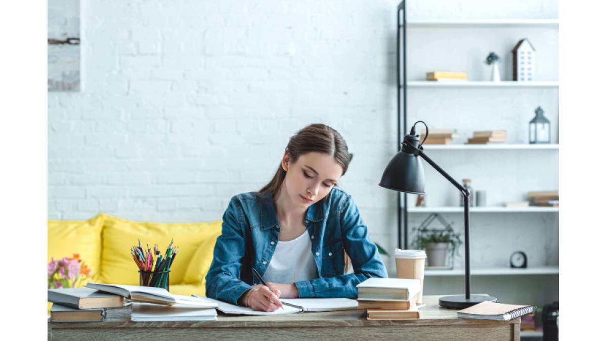 Mulher estudando em uma mesa com livros, abajur e algumas folhas